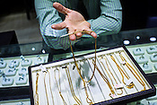 A salesman holds gold chains for a photograph at a Mehrasons Jewellers store in New Delhi, India. Photo: Sanjit Das/Panos Pictures