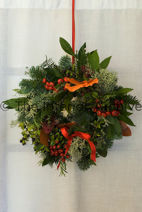 A festive Christmas wreath of berries, pine and other foliage hangs on the door