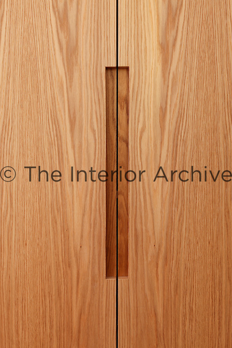 A close of up a bespoke wardrobe with flush handles.