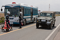 An army jeep passes a police roadblock set up on Route 6 in Minami Soma reinforce the 20 kilometre exclusion zone around Fukushima Daiich nuclear power station which was damaged in the march 11th earthquake and tsunami causing radiation leaks and explosions. Minami Soma, Fukushima, Japan. Wednesday May 4th 2011