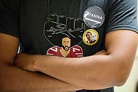 Ayanna Pressley campaign field organizer Anthony Collins, 21, of Boston, Mass., wears a shirt featuring NFL player Colin Kaepernick, a campaign button for New York 14th Congressional District Democratic candidate Alexandria Ocasio-Cortez (right lower), and a button for Ayanna Pressley, before Pressley spoke  at an event put on by Chelsea Black Community at the Chelsea Senior Center in Chelsea, Massachusetts, USA, on Wed., June 27, 2018. Pressley is running in the Democratic primary Massachusetts 7th Congressional District against incumbent Mike Capuano. Pressley is currently serving as a member of the Boston City Council, and is the first woman of color elected to the Council. Kaepernick is known for kneeling during the National Anthem before football games in protest of people who have been oppressed and has become a lightning rod for political disagreement in the US. Ocasio-Cortez won the New York 14th District Democratic primary the night before this event, unseating incumbent Rep. Joe Crowley, the 4th most powerful Democrat in the House of Representatives.