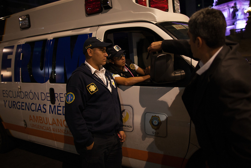 """Donovan explains his work and gives his business card to members of Mexico City's ambulance corps in Mexico City on May 25, 2015. Donovan Tavera, 43, is the director of """"Limpieza Forense México"""", the country's first and so far the only government-accredited forensic cleaning company. Since 2000, Tavera, a self-taught forensic technician, and his family have offered services to clean up homicides, unattended death, suicides, the homes of compulsive hoarders and houses destroyed by fire or flooding. Despite rising violence that has left 70,000 people dead and 23,000 disappeared since 2006, Mexico has only one certified forensic cleaner. As a consequence, the biological hazards associated with crime scenes are going unchecked all around the country. Photo by Bénédicte Desrus"""