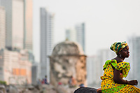 An Afro-Colombian girl, dressed in the traditional 'palenquera' costume, waits for tourists while sitting on the stone walls in Cartagena, Colombia, 11 December 2017. With the peace agreement, ending a 52-year civil conflict and promising political stability, together with rapid economic growth and unexploited tourism potential, Colombia has truly become a holiday destination. Cartagena, a UNESCO World Heritage site on the tropical Caribbean coast, plays the primary role in Colombia's tourism renaissance. The historic sites from the Spanish colonial times are being restored, private investments are visible throughout the city and an increased number of local people benefit from the boom of the travel related services.