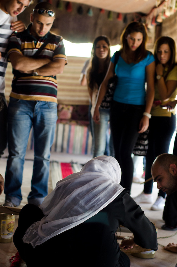 A Bedouin woman demonstrates traditonal weaving techniques at the Sidreh weaving co-operative in Lakiya, Israel, as visitors watch.