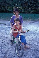Two Panamanian boys riding a bicycle in El Valle de Anton, Panama