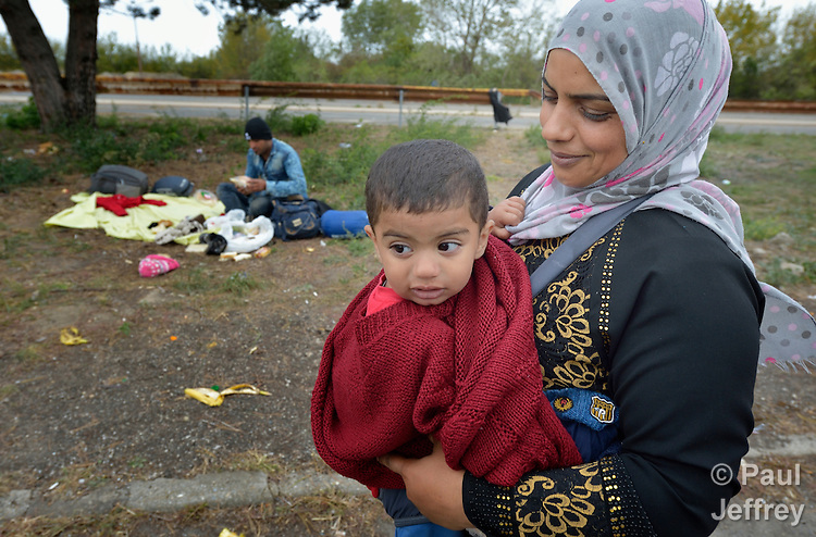 A refugee mother and child pause to rest at the border crossing into Austria near the Hungarian town of Hegyeshalom. Hundreds of thousands of refugees and migrants--including many families--flowed through Hungary in 2015, on their way to western Europe from Syria, Iraq and other countries.