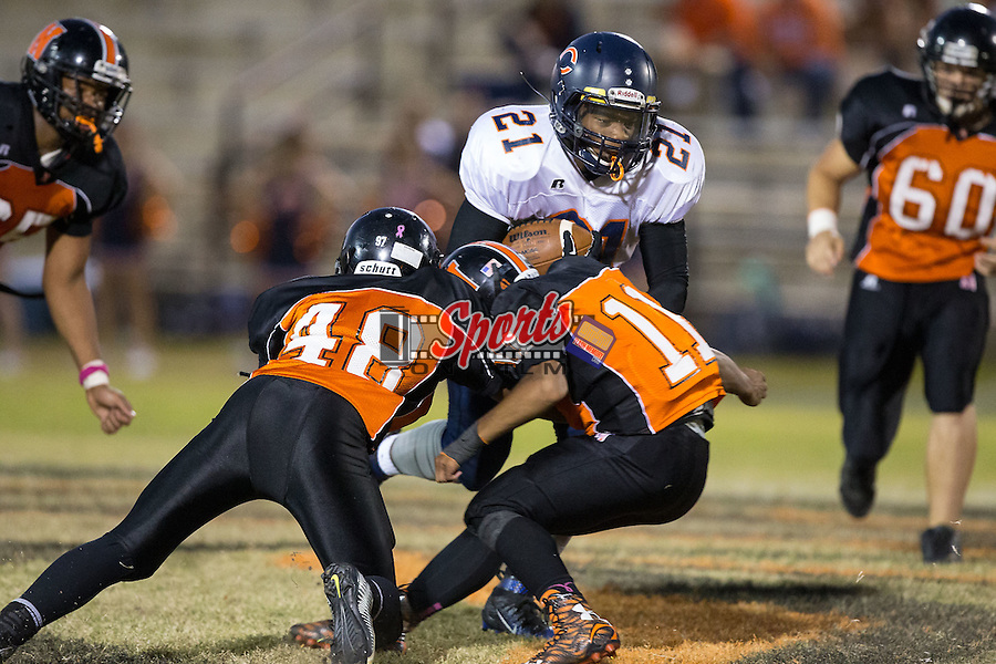 Jay Wilkerson (21) of the Carson Cougars prepares to get hit by Zecharia Phifer (48) and IJ Sturdiant (11) of the Northwest Cabarrus Trojans during first half action at Trojan Stadium October 22, 2015, in Concord, North Carolina.  The Cougars defeated the Trojans 21-20.  (Brian Westerholt/Sports On Film)