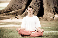 Man meditating in an outdoor park setting near large tree