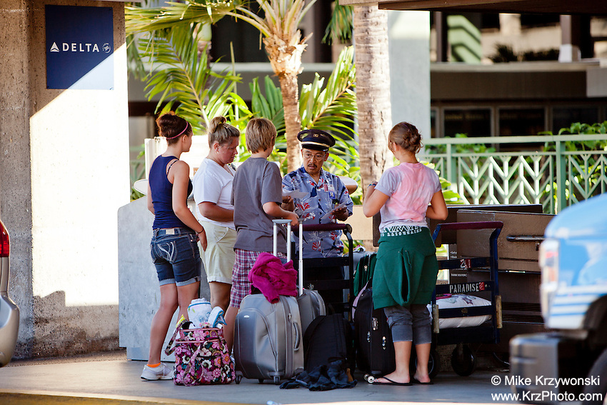 A local male airport employee assists tourists at the Honolulu International Airport, O'ahu