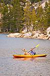 Young girl kayaking on Utica Reservoir in Alpine County, California with her dog.