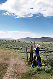 USA, Wyoming, Encampment, cowgirl closes a barbwire fence, Big Creek Ranch