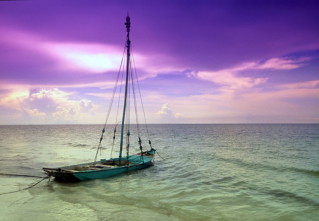 Fishing boat moored on the beach and Gulf of Mexico waters at sunset on Isa de Holbox, Mexico.