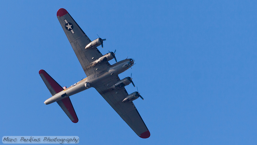 """The B-17 """"Flying Fortress"""" bomber """"Nine-O-Nine"""", tail number 231909, flying over Orange County, CA on May 12, 2013.  Taken about an hour before sunset, the bottom is clearly visible and evenly lit.  The vintage plane has been resored by The Collings Foundation to it's WWII (World War 2) configuration, after having served in nuclear bomb testing in the 1950's, being sold as scrap, and being converted into a forest-fire supression plane."""