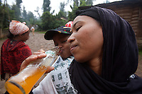 Tlbech, 27 years old, and her son Zarhiun, 4, both HIV positive share a soft drink while walking to an HIV patient during a home base care shift in Addis Ababa, ethiopia on Friday July 28 2006..Talbech and Zarihun live on a 180 birr ( 20 USD ) per month sponsorship from the HfC NGO. they spend 100 Birr for rent leaving less than 10 USD for food and other necessities. Nevertheless they are a privileged family in the country..Tlbech besides fighting againt the virus and taking care of her child provides home base care assistance in Addis to other HIV patients in need..Ethiopia is one of the countries most affected by HIV/AIDS. Of its population of 77 million, three million are HIV-positive, according to government statistics. Every day sees 1,000 new infections. A million children under 14 have lost one or both parents to AIDS, and 200,000 children are living with AIDS. That makes Ethiopia the country with the most HIV-positive children.