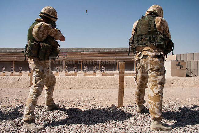An empty case flies through the air as two British Soldiers fire at targets on a range at a logistics base near Basrah City.