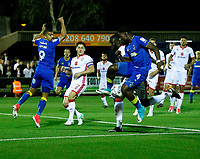The cross evades AFC Wimbledon's Adedeji Oshilaja (R) and Liam Trotter (L) during the Sky Bet League 1 match between AFC Wimbledon and MK Dons at the Cherry Red Records Stadium, Kingston, England on 22 September 2017. Photo by Carlton Myrie / PRiME Media Images.