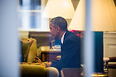 United States President Barack Obama is seen through a window of the Oval office meeting with four of the letter writers who will join the First Lady and Dr. Biden as guests of the Administration for tonightís State of the Union Address in the White House in Washington, DC, USA, 20 January 2015. Obama's State of the Union speech will include a proposal to increase taxes on the wealthy, and a proposal to require employers to provide paid sick leave to their workers.<br /> Credit: Jim LoScalzo / Pool via CNP