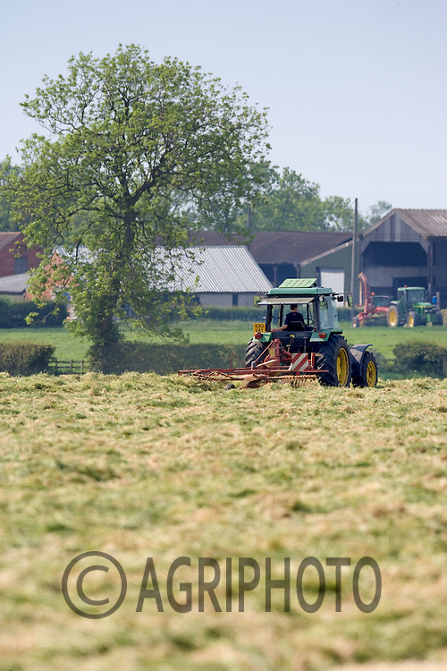Tractor Turning Grass Ready To Make Silage