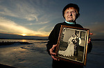 Claudia Daul LaPlante, 86, holds a 1940 photograph of her late-husband Marvin as she stands outside her home on Little Sturgeon Bay.
