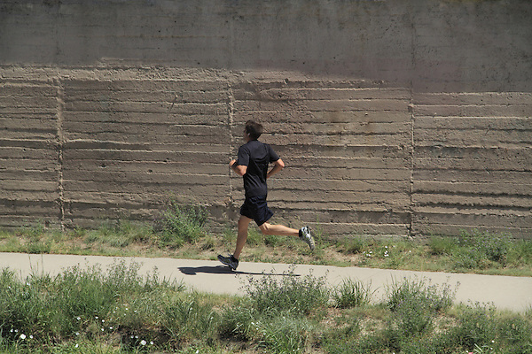 Man running on urban trail in Denver, Colorado. .  John offers private photo tours in Denver, Boulder and throughout Colorado. Year-round Colorado photo tours.