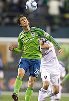 Seattle Sounders midfielder Alvaro Fernandez heads the ball as he is pushed by L.A. Galaxy forward Landon Donovan during play at Qwest Field in Seattle Tuesday March 15, 2011. The Galaxy won the game 1-0.