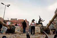 A man stands on an abandoned army tank amidst clashes between anti-government protesters and pro-Mubarak supporters outside the Egyptian Museum in Tahrir Square. Continued anti-government protests take place in Cairo calling for President Mubarak to stand down. After dissolving the government, Mubarak still refuses to step down from power.