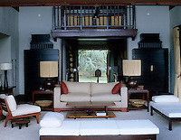 The main door opens onto the living room which is furnished with pieces made by local craftsmen such as the mahogany cabinets that flank the entrance