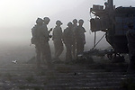Canadian soldiers from November Company, 3rd Battalion, Royal Canadian Regiment, stand near their Light Armored Vehicle amid a cloud of late-afternoon dust at the start of a week-long operation around the village of Nakhonay, southwest of Kandahar, Afghanistan. Oct. 5, 2008. DREW BROWN/STARS AND STRIPES