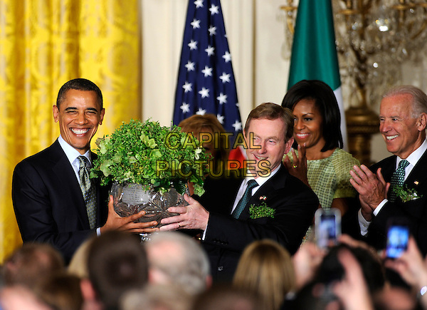 United States President Barack Obama (L) accepts a bowl of shamrocks from Irish Prime Minister Enda Kenny as first lady Michelle Obama (2nd,R) and Vice President Joe Biden (R) during a reception in the East Room of the White House, March 20, 2012, in Washington, DC. The two leaders concluded a working day devoted to discussions on economic matters, Ireland's peace keeping participations and foreign policy issues like Syria and Iran. .half length black suit flowers plant pot.CAP/ADM/MT.©Mike Theiler/Pool/CNP/AdMedia/Capital Pictures.
