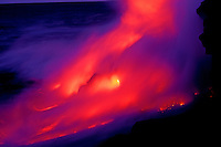 Swirling ethereal pink and purple tinged clouds rise from the impact of lava flowing into the ocean off the Puna coast, Volcanoes National Park, Hawaii.