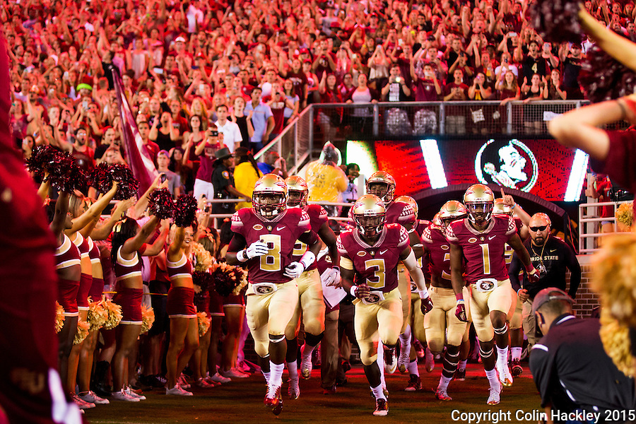 TALLAHASSEE, FLA. 9/5/15-Kermit Whitfield (8), left, Jesus Wilson (3), and Ermon Lane (1) lead the Seminoles on to the field to open the curtain on the 2015 football season just before the Florida State University vs. Texas State University football game at Doak Campbell Stadium in Tallahassee.<br /> <br /> COLIN HACKLEY PHOTO