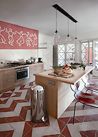 The contemporary kitchen is connected to the living room by a wall of reclaimed glass doors and has a bold herringbone tiled floor