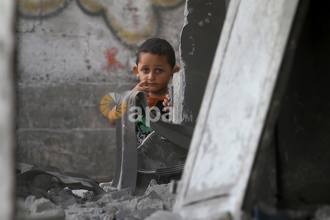 A Palestinian boy stands on the rubble of the destroyed houses and buildings that were destroyed during the devastating 50-day war between Israel and Hamas at Al-Shojae'ya neighborhood east of Gaza City on October 11, 2014. ahead of a donors conference in Cairo aimed at gathering efforts to the reconstruction of the Gaza Strip after the devastating 50-day war between Israel and the Hamas militants who run the coastal Palestinian enclave. The Palestinian government has unveiled a 76-page reconstruction plan for Gaza, calling for $4 billion to rebuild the war-battered territory, with the largest amount going to build housing for some 100,000 left homeless. Photo by Mohammed Asad