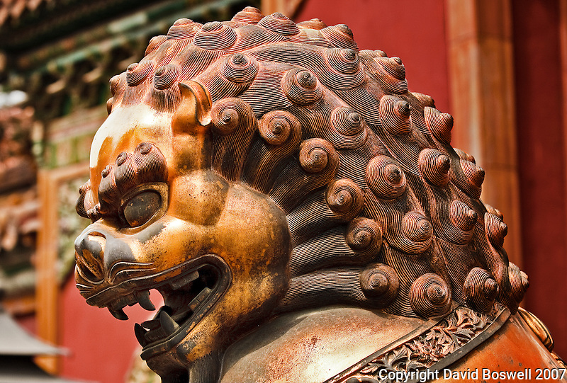 A bronze sculpture of a lion, guarding the Forbidden City in Beijing, China.