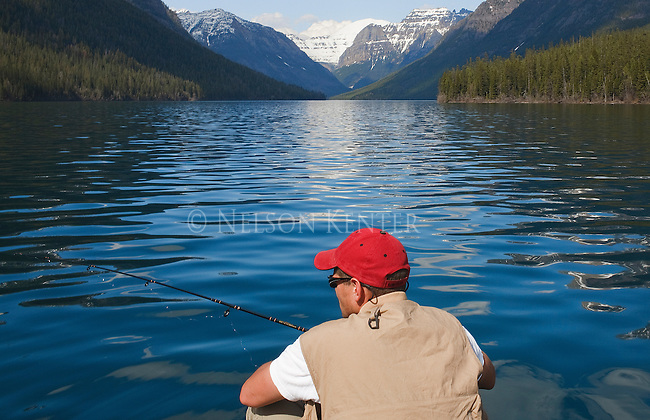 A fisherman on Bowman Lake in Glacier National Park in Montana with snow capped mountain peaks at the head of the lake