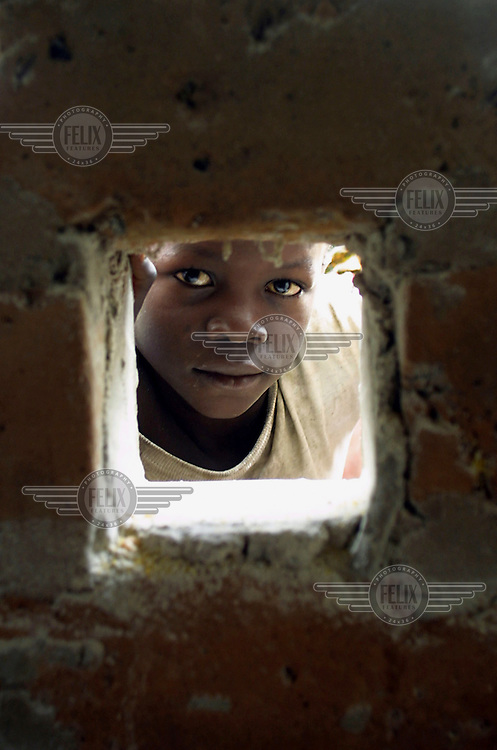 A Congolese refugee looks through a hole in the wall of a hammer mill, used to grind corn in the Kala refugee camp.