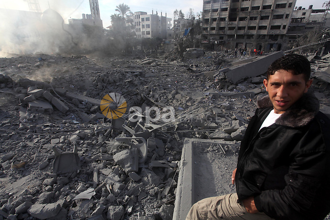A Palestinian looks at government offices destroyed in an Israeli airstrike in Gaza City, 21 November 2012. Palestinian militants renewed their rocket fire on Israel 21 November and Israel continued pounding targets in the Gaza Strip, as agreement on a hoped-for truce remained elusive. The Israeli military said it bombed around 100 targets in the Strip overnight, including 50 underground rocket launchers. Photo by Ashraf Amra