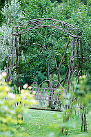 A view through plants of the wrought-iron double swing seat in the orchard