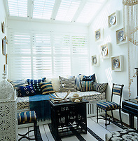 The conservatory has a black, white and blue colour scheme and an assortment of ethnic and blue and white vintage cushions scattered on the banquette