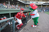 Catcher Jordan Procyshen (29) of the Greenville Drive bumps fists with mascot Reedy Rip'It as he is introduced before a game against the Lexington Legends on Sunday, August 31, 2014, at Fluor Field at the West End in Greenville, South Carolina. Greenville won, 3-2. (Tom Priddy/Four Seam Images)