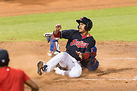 AZL Indians 1 right fielder Johnathan Rodriguez (30) looks to home plate umpire Glen Meyerhofer (not pictured) after sliding across home plate ahead of the tag from catcher David Garcia (9) during an Arizona League playoff game against the AZL Rangers at Goodyear Ballpark on August 28, 2018 in Goodyear, Arizona. The AZL Rangers defeated the AZL Indians 1 7-4. (Zachary Lucy/Four Seam Images)