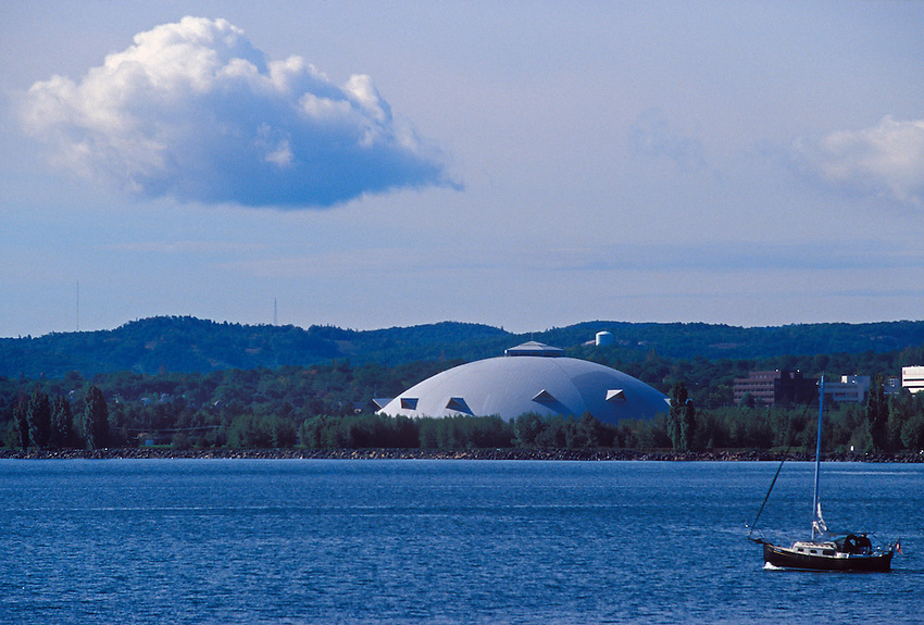 A sailboat motors out onto Lake Superior in Marquette, Mich. with a cloud and the NMU Superior Dome in the background.