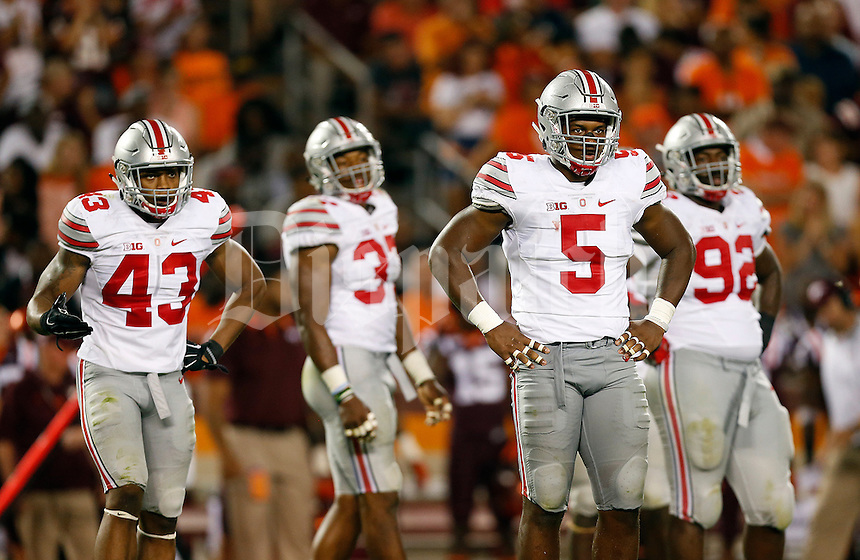 Ohio State defensive players, from left, linebacker Darron Lee (43), linebacker Joshua Perry (37), linebacker Raekwon McMillan (5) and defensive lineman Adolphus Washington (92) look to the sideline for the play call during the NCAA football game against Virginia Tech at Lane Stadium in Blacksburg, Virginia on Sept. 7, 2015. Ohio State won 42-24. (Adam Cairns / The Columbus Dispatch)