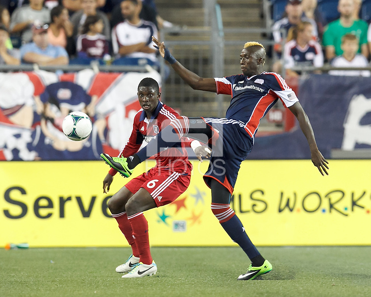 New England Revolution substitute midfielder Saer Sene (39) collects a pass as Chicago Fire defender Jalil Anibaba (6) closes. In a Major League Soccer (MLS) match, the New England Revolution (blue) defeated Chicago Fire (red), 2-0, at Gillette Stadium on August 17, 2013.