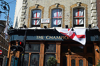 23rd April 2020, London, United Kingdom; The Champion Pub with the flags of England or St. George's Cross draped across it to celebrate St. George's Day in Wells Street, London, England, UK on Thursday 23 April, 2020. With Pubs shut, there are no celebrations outside the pub.