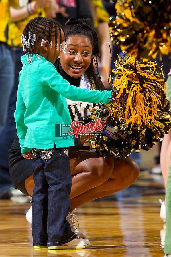 A young fan shakes her pom pom with a Wake Forest Demon Deacons cheerleader during a timeout against the Georgia Tech Yellow Jackets at the Lawrence Joel Coliseum on January 13, 2011 in Winston-Salem, North Carolina.  The Yellow Jackets defeated the Demon Deacons 54-46.  Photo by Brian Westerholt / Sports On Film