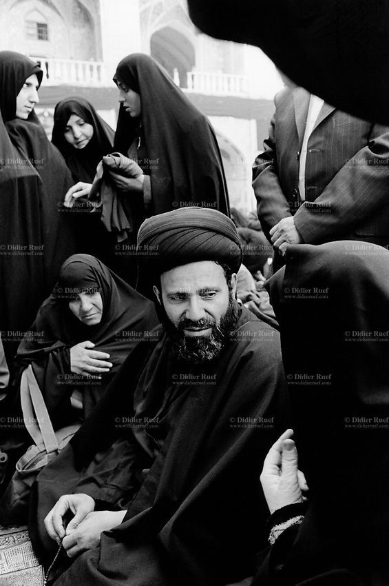 Iraq. Najaf. A mollah (Emam Hassen Al-Hamamy) talks to a group of iraqi women after the midday prayer inside the mosque, Holy Shrine of Imam Ali. The women wear the abaya and the hijab (islamic headscarf) on their heads to cover their hair. The abaya, sometimes also called aba, is a simple, loose over-garment, essentially a robe-like dress, worn by some women in parts of the Islamic world. Traditional abaya are black and may be either a large square of fabric draped from the shoulders or head or a long caftan. The abaya covers the whole body except the face, feet, and hands. The mullah is generally used to refer to a Muslim man, educated in Islamic theology and sacred law. The title, given to some Islamic clergy, is the name commonly given to local Islamic clerics or mosque leaders.26.02.04  © 2004 Didier Ruef.