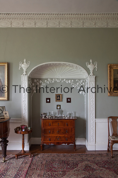 Ornate plasterwork swags and delicate vines, in the classical style, decorate the ceiling and alcove in the drawing room