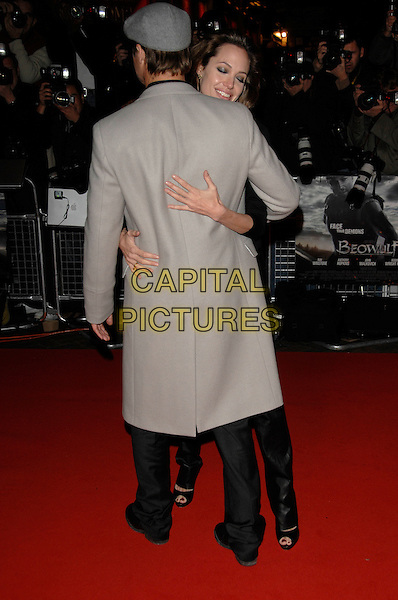 "BRAD PITT & ANGELINA JOLIE.""Beowulf"" European film premiere.Vue cinema, Leicester Square, London, England.11th November 2007.full length black leather trousers grey hat cap coat couple back hug hugging.CAP/PL.©Phil Loftus/Capital Pictures"