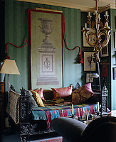 An ornate cast-iron daybed in the living room is covered with short lengths of different textiles forming a fabric mosaic